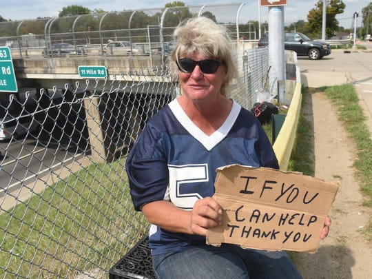 Joann Poff, who is homeless, sits near I-75 at 12 Mile in Madison Heights.