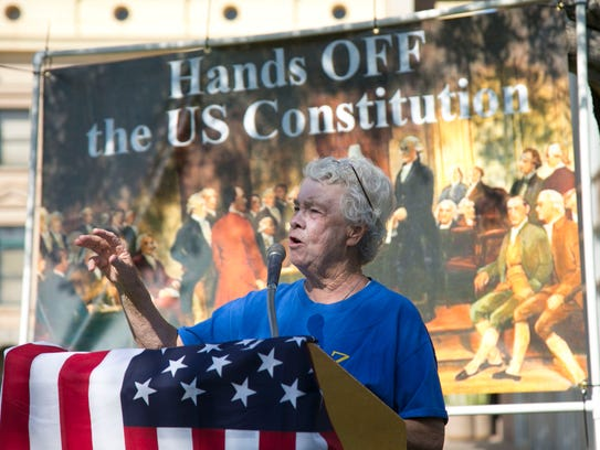 Anne Schneider of Phoenix speaks during a rally protesting
