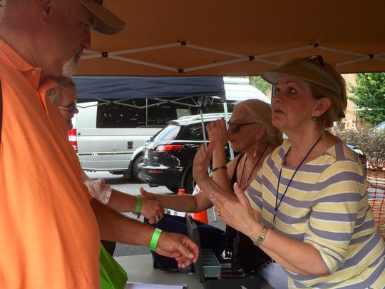 Volunteers answer questions as people come into the Shenandoah Valley Blues and Brews Festival on Saturday.