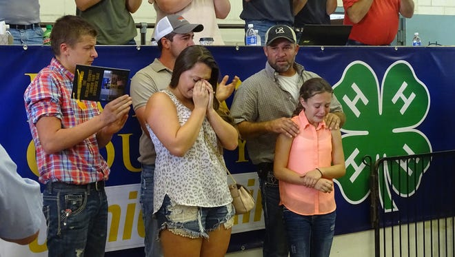 The family of Walker Ramsay reacts to a standing ovation during Aug. 13's Richland County Junior Fair livestock sale.
