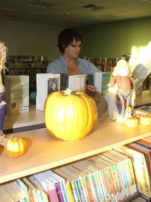 Shelly Given, an aide at the library, arranges books on the shelf at the Springmier Community Library in Tiffin. Located on the campus of Clear Creek Amana Middle School, voters will be deciding a levy to expand library services Nov. 7.