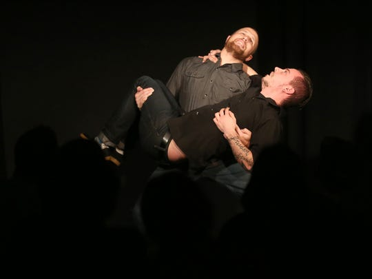 Jared Richard carries Reverend Buerge during an improv comedy show at the Capitol City Theater.