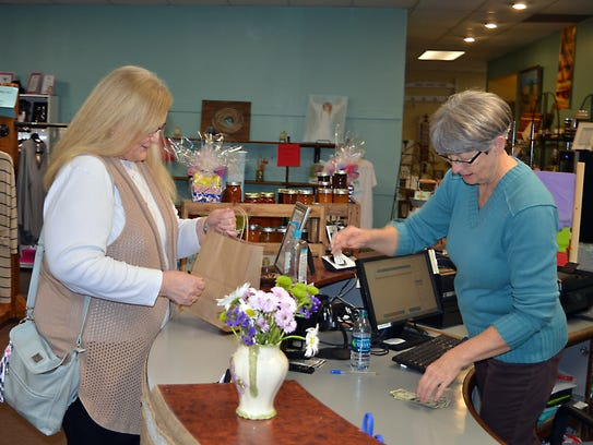 Sharon Ivy, right, assists customer Sandra Latham,