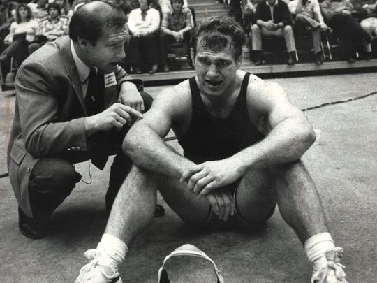 Iowa coach Dan Gable (left) talks to Ed Banach during a college match. Both won Olympic gold medals.