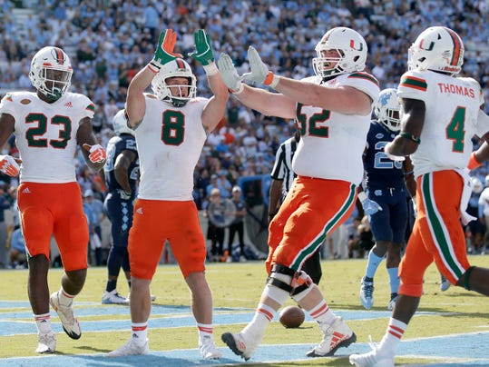 Miami's Braxton Berrios (8) celebrates his touchdown with Christopher Herndon IV (23), KC McDermott (52) and Jeff Thomas (4) during the second half of an NCAA college football game against North Carolina in Chapel Hill, N.C., Saturday, Oct. 28, 2017. Miami won 24-19. (AP Photo/Gerry Broome)