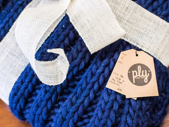 A hand-knitted throw blanket is seen at Ply Fiber Arts,