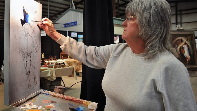 Graham artist Beth Prichard works on an oil painting of a bronc rider as she prepares for the 6th Annual Cowboy True at the Bridwell Ag Center.