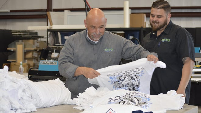 Rigo Aguirre, left, works alongside his son Ryan Aguirre at Aguirre Printing and Embroidery, 9610 W. Nicholas St. on Wednesday. Aguirre Printing is celebrating 20 years of business this month.