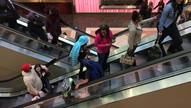 Shoppers take an escalator at Mayfair mall in Wauwatosa. The mall was filled with shoppers, but parking spots could still be easily found on the northeast side of the mall.