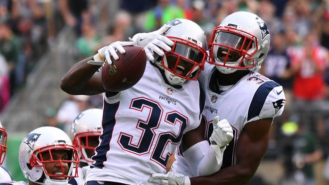 The New England Patriots safety Devin McCourty (32), celebrates with safety Duron Harmon (30) against the New York Jets during the second half at MetLife Stadium.