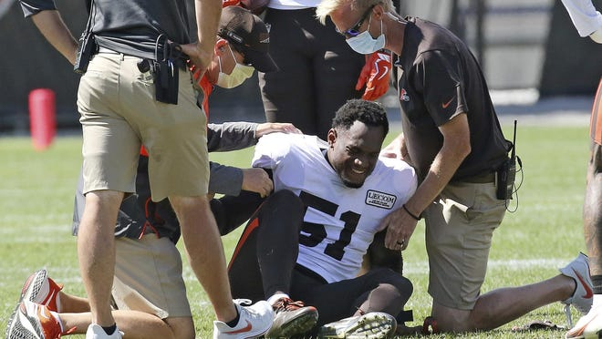 Cleveland Browns linebacker Mack Wilson is helped up by the team's medical staff after suffering a knee injury in a 7-on-7 drill during training camp, August 18, 2020, in Berea, Ohio.