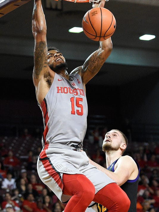 Houston forward Devin Davis, left, dunks as East Carolina forward Dimitri Spasojevic, right, watches during the first half of an NCAA college basketball game, Sunday, Feb. 25, 2018, in Houston. (AP Photo/Eric Christian Smith)