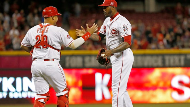 Reds closer Aroldis Chapman (right) and catcher Brayan Pena shake hands after Tuesday's 4-2 win against the Brewers.
