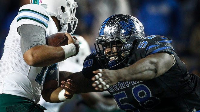 Memphis defensive lineman Donald Pennington (right) brings down Tulane quarterback Jordy Joseph (left)  during second quarter action at  Liberty Bowl Memorial Stadium on Oct. 31, 2015.