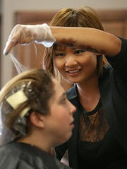 Emily Chen works through layers of hair and layers of color as she treats the hair of client Krystine Quigley, Canandaigua, at the Allora Salon & Spa in Victor Wednesday, March 25, 2015.
