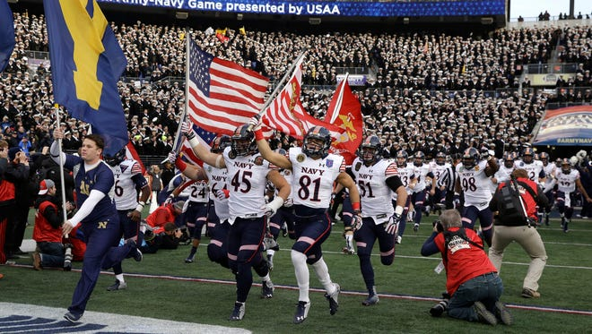Navy's football team runs onto the field before last season's Army-Navy Game in Baltimore.