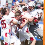 Denver Pioneers goalie and Fort Collins High School graduate Ryan LaPlante (10) is mobbed by his team in celebration of defeating the Maryland Terrapins to win NCAA division I men's lacrosse championship game at Lincoln Financial Field. The Denver Pioneers won 10-5.