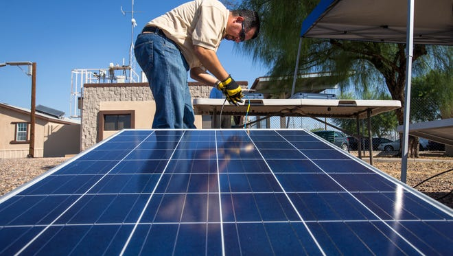 Jimi Diaz, an APS solar operations electrical engineer, adjusts the connection of a solar panel to a power output meter, at the APS STAR Center at the Ocotillo Power Plant in Tempe.