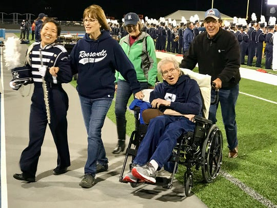 Dan Miller, seated, died before he could see his daughter, Maya Miller, far left, graduate from Roosevelt High School. But he made it to senior night for the marching band. His wife, Diane Graham, is to his immediate left.