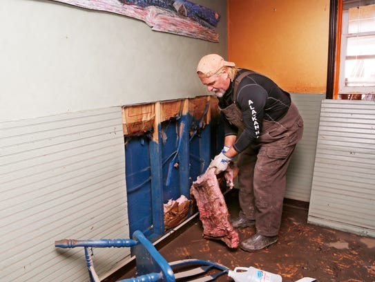 Jeff Seramur pulls wet insulation from the wall of