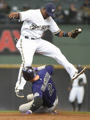 Colorado Rockies shortstop Troy Tulowitzki slides safely into second base with a double as Milwaukee Brewers shortstop Jean Segura fields the relay in the third inning at Miller Park on Monday.