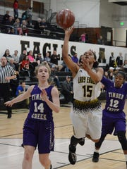 Abilene High's Triniti Wilson shoots a floater in the lane in front of Keller Timber Creek's Kristen Gould (14) and Lanae Johnson-Kleinpeter (12) during the Lady Eagles' 49-36 loss Tuesday at Eagle Gym.