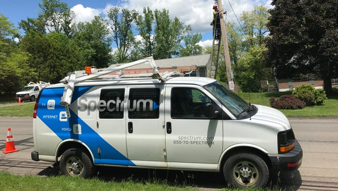 A Spectrum worker climbs a utility pole on Saturday, June 3, 2017 on Vestal Avenue, BInghamton. Spectrum, a unit of Charter Communications, acquired Time Warner Cable last year.