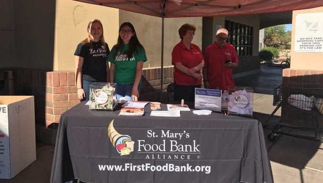 Annie Gignoux (from left), Sasha Perez, Shelly Dudley and Larry Schumitz collect donations for St. Mary's Food Bank Super Saturday Turkey Drive outside a Phoenix Safeway on Nov. 18, 2017.