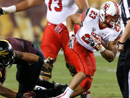 Utah's Devontae Booker looks to break through the ASU defense in the first half on Saturday, Nov. 1, 2014, in Tempe.