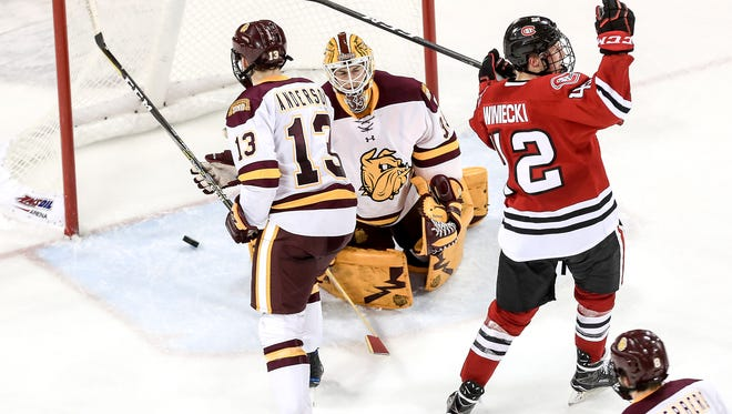 St. Cloud State center Blake Winiecki (42) celebrates after scoring a goal against Joey Anderson (13) and Hunter Miska (35) of Minnesota Duluth during Saturday's game at Amsoil Arena in Duluth. Minnesota Duluth defeated St. Cloud State 4-3 in overtime.