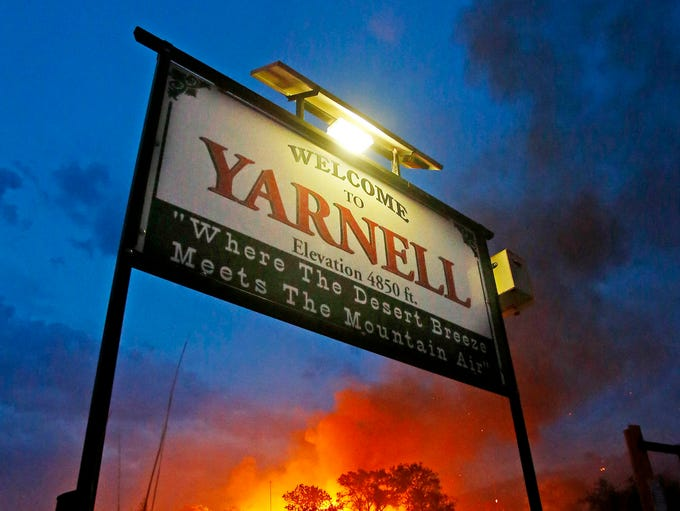 """The Yarnell Hill Fire burns structures behind the  """"Welcome to Yarnell"""" sign."""