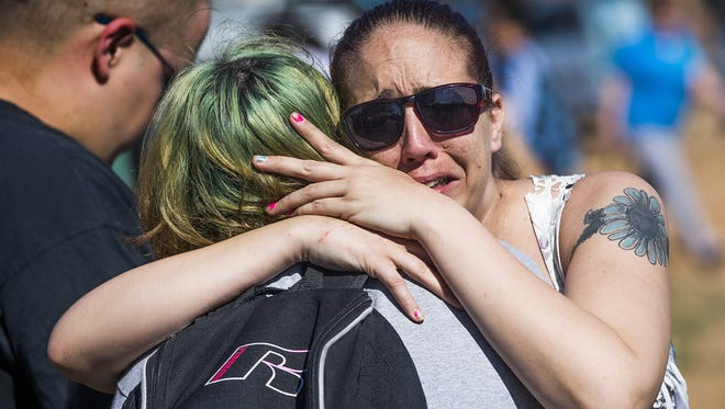 Abbie Olsen hugs her son, David Orca, 17, a student at Independence High School Friday morning after two students were shot and the campus was locked down.