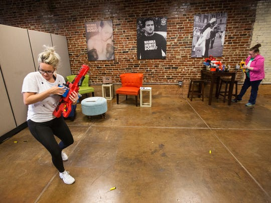 Kas Clegg, left, co-owner and CMO at Hurts Donut, and Jessica Nottingham, corporate office manager, scramble to reload their Nerf guns at the Hurts Donut corporate office in downtown Springfield on Monday, November 28, 2016.