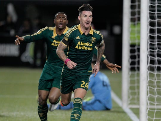 Portland Timbers forward Fanendo Adi (9) and defender Liam Ridgewell (24) celebrate Ridgewell's goal during the first half of the first leg of the MLS soccer Western Conference championship in Portland, Ore., Sunday, Nov. 22, 2015.