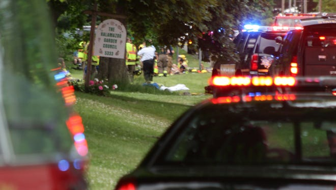 Emergency workers cluster around the five victims of a collision between a pickup truck and nine bicyclists Tuesday evening on North Westnedge Avenue north of Kalamazoo.