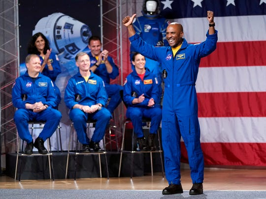 Astronaut Victor Glover raises his arms after being