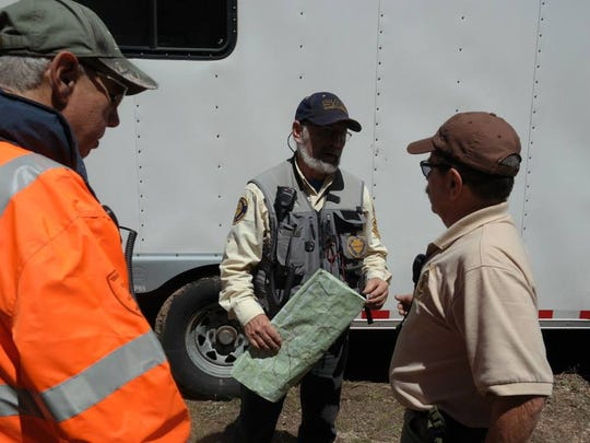 Searchers brief each other before continuing efforts