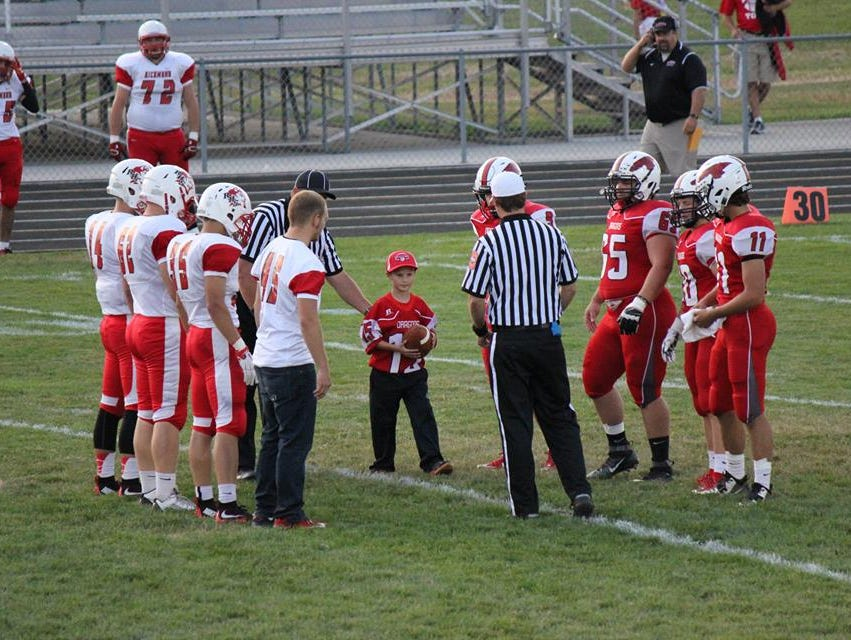 Eight-year-old Clayton Trebley holding the game ball before the New Palestine Dragons game.