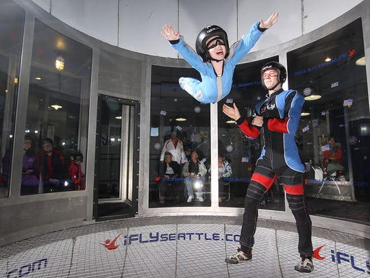 Kids can fly! A child flies at iFLY  as her instructor spots her.