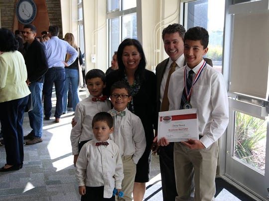 A project winner poses with his family members after Sunday's awards ceremony.
