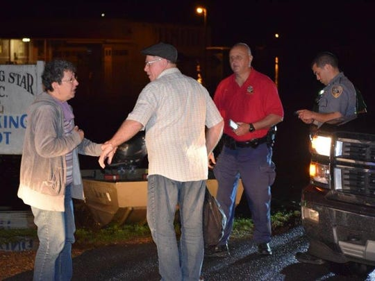 Two unidentified French tourists (left) react after being rescued from high water in Natchez Thursday night by the Natchitoches Parish Sheriff's Office and two citizens.