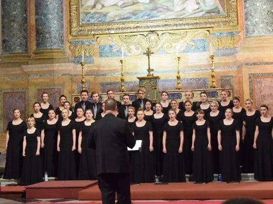 Brighton High School choir director Phil Johnson directs the choir in a church in Italy this week.
