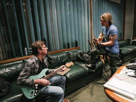 Keith Urban and Dann Huff work in the recording studio.