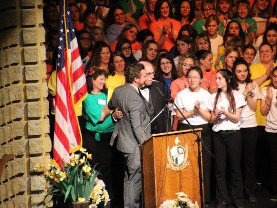 Howell High School Principal Jason Schrock hugs former