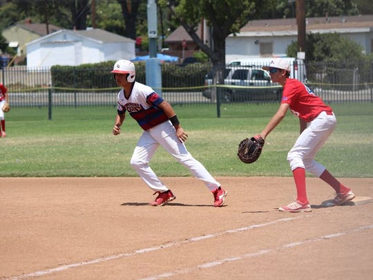 A La Quinta Scorpions baseball player takes a lead off first base as the team strives to earn a World Series berth.