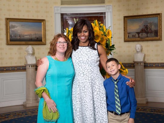 "McLean Knight, 10, right, of Las Cruces, state winner of a contest that promotes healthful cooking, is seen with First Lady Michelle Obama on July 14 during the ""Kids' State Dinner"" at the White House. Kristin Knight, left, McLean's mom, accompanied him on the trip."