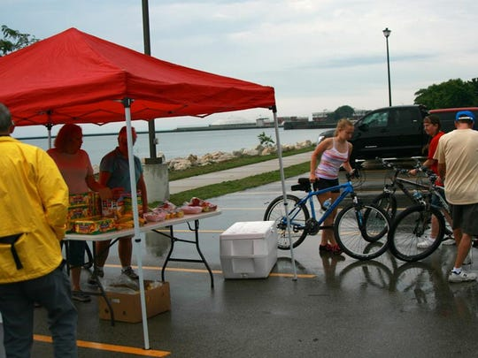 Cyclists stop at a rest stop where volunteers hand out fruit and water during the 2014 Ride For Hunger.