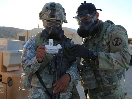 1st Brigade soldiers use a chemical detector following