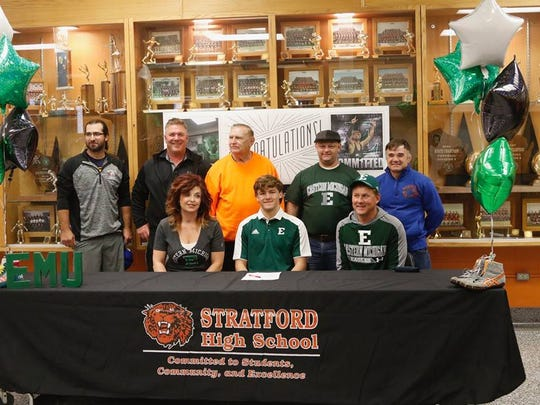 Joe Ramsey, back row far right, has worked with Mason Kauffman, center sitting, who signed his letter of intent this fall to wrestle at Eastern Michigan University.