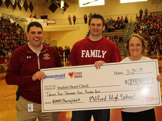 """Jennifer Shea, manager of Beaumont Student Heart Check, accepts a symbolic """"big check"""" from Kevin McKenna, Milford High School principal,  (left) and teacher David Gilbert. Students raised $24,404 for the heart assessment program."""